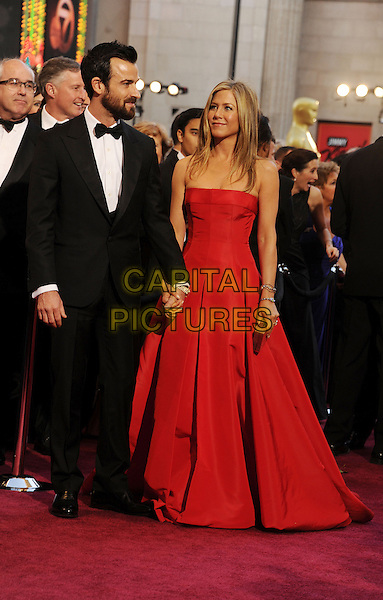 Justin Theroux & Jennifer Aniston (wearing Valentino).85th Annual Academy Awards held at the Dolby Theatre at Hollywood & Highland Center, Hollywood, California, USA..February 24th, 2013.oscars full length black tuxedo white shirt bow tie beard facial hair red strapless dress gown couple engaged silver clutch bag holding hands profile .CAP/ROT/TM.©Tony Michaels/Roth Stock/Capital Pictures