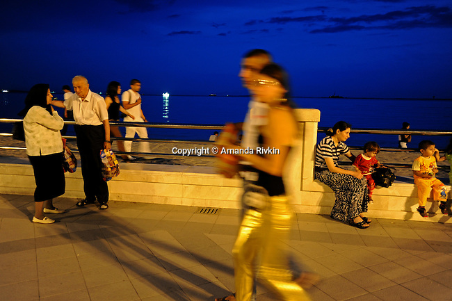 Bakuvians are seen promenading on the Bulvar of Baku, Azerbaijan on July 15, 2010. Bulvar is the Caspian seaside walkway that traces the luxurious center of central Baku and is a local favorite place to promenade.
