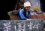 Ba woman farmer weathered by the years wearing traditional headwear at wall along road in Three Gorges area of rural China, Asia