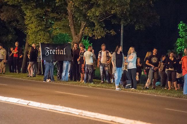 Nach den pogromartigen Ausschreitungen gegen eine Fluechtlinsunterkunft im saechschen Heidenau am Freitag den 21. August 2015 durch Anwohnerinnen der Ortschaft, kamen am Samstag de 22. August 2015 ca. 250 Menschen in die Ortschaft um ihre Solidaritaet mit den Gefluechteten zu zeigen.<br /> Am Vorabend hatten Rassisten, Nazis und Hooligans sich zum Teil Strassenschlachten mit der Polizei geliefert um zu verhindern, dass Fluechtlinge in einen umgebauten Baumarkt einziehen. Ueber 30 Polizisten wurden dabei verletzt.<br /> Bis in die Abendstunden des 22. August blieb es trotz spuerbarer Anspannung um die Unterkunft ruhig. Im Laufe des Tages wurden immer wieder Gefluechtete mit Reisebussen gebracht was von den wartenenden Heidenauern mit Buh-Rufen begleitet wurde. Vereinzelt wurde auch &quot;Sieg Heil&quot; gerufen, was die Polizei jedoch nicht verfolgte.<br /> Kurz vor 23 Uhr griffen Nazis und Hooligans wie am Vorabend die Polizei mit Steinen, Flaschen, Feuerwerkskoerpern und Baustellenmaterial an. Die Polizei mussten mehrfach den Rueckzug antreten, scheuchte den Mob dann von der Fluechtlingsunterkunft weg. Dabei wurden auch wieder Traenengasgranaten verschossen. Mindestens ein Nazi wurde festgenommen.<br /> Im Bild: Ein Rassist haelt eine Fahne &quot;Freital&quot;, einem 20 Km enfernter Ort, in dem auch Rassisten gewaltbereit gegen Gefluechtete vorgingen.<br /> 22.8.2015, Heidenau/Sachsen<br /> Copyright: Christian-Ditsch.de<br /> [Inhaltsveraendernde Manipulation des Fotos nur nach ausdruecklicher Genehmigung des Fotografen. Vereinbarungen ueber Abtretung von Persoenlichkeitsrechten/Model Release der abgebildeten Person/Personen liegen nicht vor. NO MODEL RELEASE! Nur fuer Redaktionelle Zwecke. Don't publish without copyright Christian-Ditsch.de, Veroeffentlichung nur mit Fotografennennung, sowie gegen Honorar, MwSt. und Beleg. Konto: I N G - D i B a, IBAN DE58500105175400192269, BIC INGDDEFFXXX, Kontakt: post@christian-ditsch.de<br /> Bei der Bearbeitung der Dateiinf