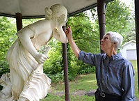 """NWA Democrat-Gazette/ANDY SHUPE<br /> Joyce Hale of Fayetteville discusses Tuesday, May 7, 2019, the sculpture """"Nydia, The Blind Flower Girl of Pompeii"""" by Randolph Rogers as it stands in the backyard of the Hales' Fayetteville home. The statue was purchased from the Diana Hotel in Springdale in the 1970s."""
