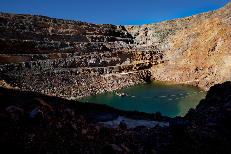 """Mountain Pass, California, November 15, 2010 - A barge, which operates as a sort of sump pump, pumps water out of the open pit mine at Mountain Pass, owned by Molycorp Minerals, which mines rare earth elements. According to Scott Honan, an Environmental Manager for Molycorp, the company has been pumping for six months and has another month to go before it is dry. """"The mine is currently about 500 feet deep. We plan to go another 300 feet. But the water has to come out first,"""" said Honan. It is estimated that the mine contains some 20 million tons of ore.  """"When we resume mining operations, we will be able to mine 2 tons of earth per day, with about an 8% yield of rare earth,"""" Honan added. Rare earth elements - there are 17 in all - are crucial for many current technologies, including mobile phones, wind turbines, hybrid cars, laptops and military hardware, such as Army tank navigation systems and Navy radars. Uranium prospectors discovered the mine at Mountain Pass in 1949 and it became the dominant producer of rare earth elements until the 1990s when pressure from other producers began to drive prices down. That along with a number of leaks of radioactive water during transmission into a evaporation lake 13 miles away and state regulators delaying operating permits forced the mines closure in 2002. Though mining ceased, some processing of already mined elements continued. Molycorp was purchased by Unocal in the 1970s, which in turn was purchased from Chevron. In 2008 it's long-time chief executive, Mark A Smith, purchased in from Chevron with the help of several private equity firms. The company raised $500 million in an effort to reopen the mine, which will include expanding and modernizing the current facilities as well as incorporating newer technologies to make mining the radioactive material more environmentally safe and adding a natural gas power plant to help reduce its need to buy more expensive and less reliable energy from Los Angeles.  ."""