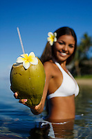 Smiling, attractive local girl standing in the ocean, holds out a coconut with straw and flower ready to drink at Lahaina, Maui, Hawaii.