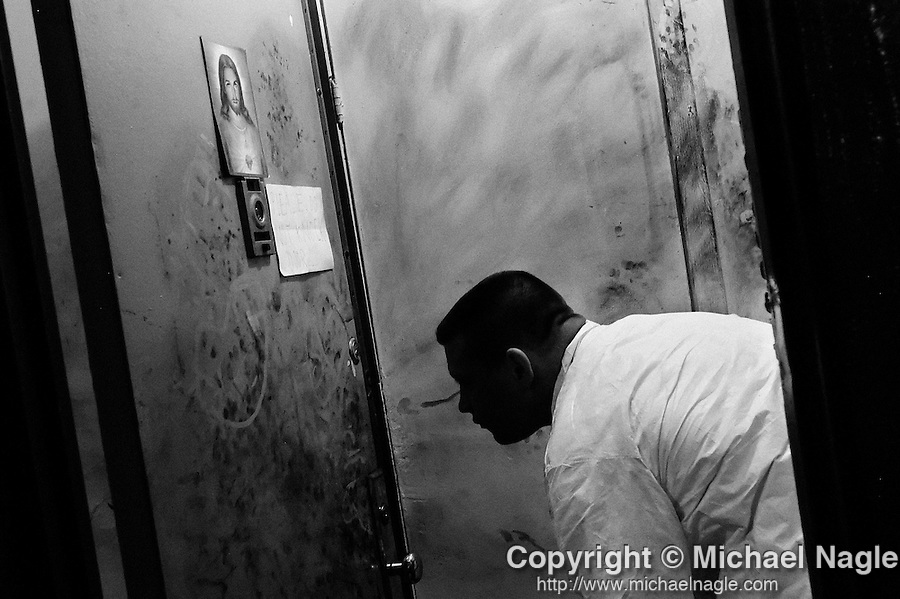 BROOKLYN -- DECEMBER 29, 2004: An NYPD detective looks for fingerprints at an apartment where Luciano Yevenes was stabbed to death in a person dispute, on December 29, 2004 in the 77th Precinct of Brooklyn. While murders are down again in New York this year, hot spots persist, and the 77th is among the top 10. (PHOTOGRAPH BY MICHAEL NAGLE).