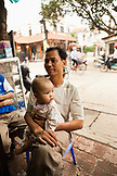 VIETNAM, Hanoi, Bathranag Village, a man sits with his daughter at a small street side restaurant