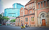 VIETNAM, Ho Chi Minh, Saigon, People driving motorcycles in front of Saigon Notre Dame Basilica, Diamond Plaza Shopping Mall in the background