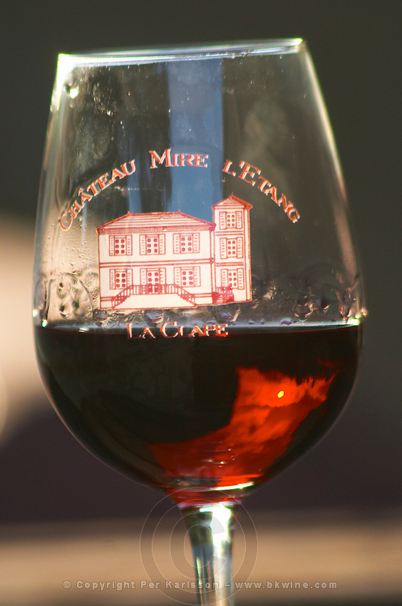 Glass of red wine embossed with Chateau Mire l'Etang La Clape. Reflection of the sky and sun in the glass. Chateau Mire l'Etang. La Clape. Languedoc. France. Europe.