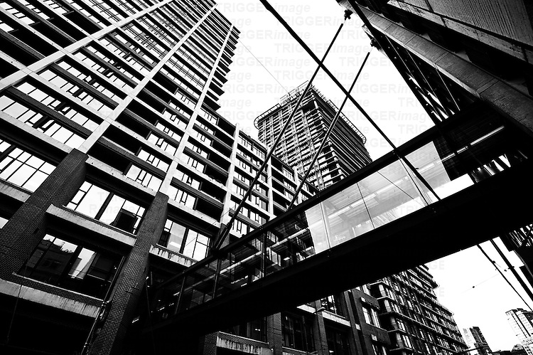 Criss crossing overhead walk ways amongst crowded skyscrapers in a downtown city neighbourhood.
