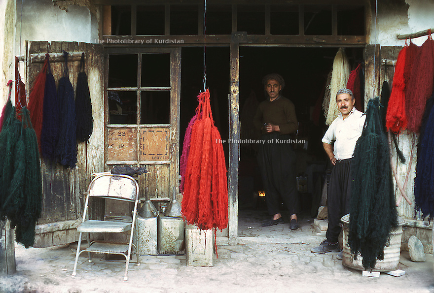 Iran 1975.Mahabad: Men in front their shop selling wool
