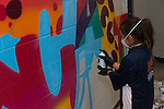 Garden Villas student works diligently on the mural.