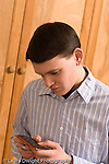 Teenage boy 19 years old using cell telephone to text message texting vertical Caucasian