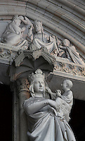 Low angle view from the side of the statue of Virgin and Child decorating the trumeau of the portal to the lower chapel of La Sainte-Chapelle (The Holy Chapel), 1248, Paris, France. Above, the tympanum depicting the coronation of the Virgin is visible. La Sainte-Chapelle was commissioned by King Louis IX of France to house his collection of Passion Relics, including the Crown of Thorns. It is considered among the highest achievements of the Rayonnant period of Gothic architecture. Picture by Manuel Cohen