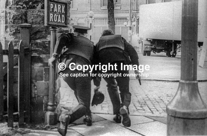 Policemen, with guns drawn, chase hooded hijackers at the junction of Park Road and Ormeau Road, Belfast, N Ireland, 16th May 1974. 197405160367<br />