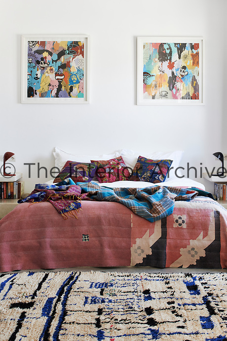 The bedroom has a double bed with side shelves with lamps and patterned cushions and bed cover. Colourful prints on the wall and a pattern rug complete the picture.