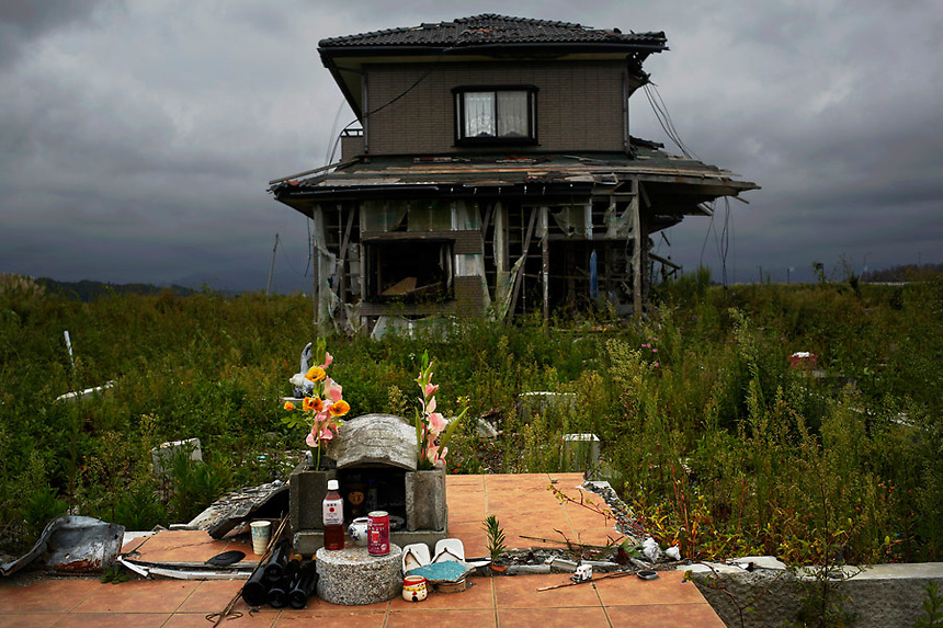 A small monument to victims is seen in front of abandoned house at the tsunami destroyed coastal area of the evacuated town of Namie in Fukushima prefecture only some 6 kilometers from the crippled Daiichi power plant September 22, 2013. Namie's more than 20,000 residents can visit their homes once a month with special permissions but are not allowed to stay overnight inside the exclusion zone. A total of 160,000 people had been forced to leave their homes around Daiichi plant after the government ordered the evacuation following the nuclear disaster in March 2011.  REUTERS/Damir Sagolj (JAPAN)