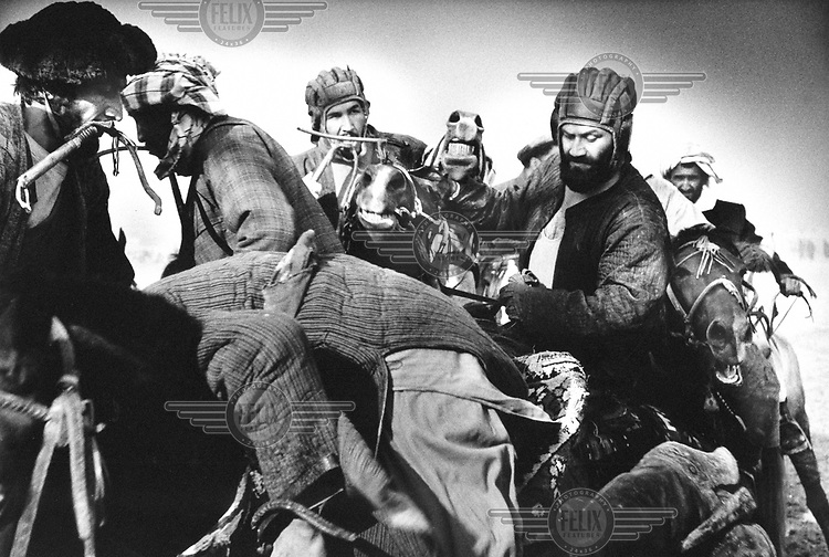 """© Tim Dirven / Panos Pictures..Mazar-e-Sharif, Afghanistan. December 2001...Buzkashi is Afghanistan's national sport. Literally translated as """"goat grabbing"""", it is played by two teams of men on horseback. They battle for control of a headless goat's carcass, with the objective of getting the carcass to a scoring circle. The game is said to date from the days of Genghis Khan, and remained popular despite being declared un-Islamic by the Taliban. To many Afghans, Buzkashi is not just a game, it is a way of life."""