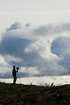 A man films the Iceland clouds and landscape. The man was part of a team that was filming the Cape Farewell Youth Expedition organized by the British Council of Canada.
