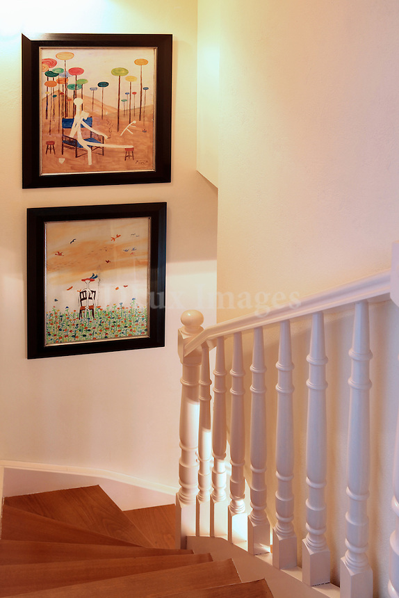 wooden staircase with modern paintings