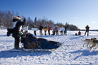 Kelley Griffin runs past some of her fans with well-wishing signs  on Long Lake during the restart of Iditarod 2012