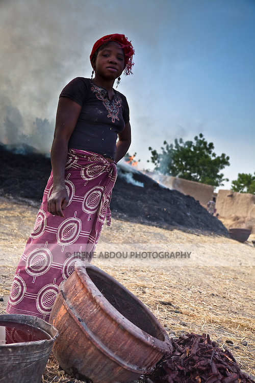In the village of Kalabougou near Segou, Mali, women of the numu blacksmiths population have worked for centuries as traditional potters.  Next to the kilns, a woman separates the red bark of a certain tree from the water it has been soaked in.  The red-dyed water will be used as a decorative glaze for the pots yet to be fired.  The glaze is most often applied to the neck of the pot.