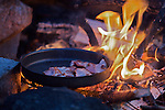 Making bacon on a fire burning at night deep in the woods outside Oslo, Norway