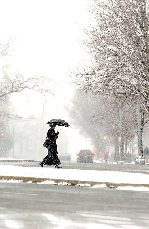snow/012103 -- A woman crosses Constitution Ave., NE, during tuesday's snow fall.