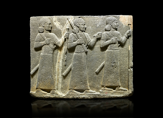 Hittite relief sculpted orthostat stone panel of Royal Buttress Basalt, Karkamıs, (Kargamıs), Carchemish (Karkemish), 900-700 B.C. Warriors. Anatolian Civilisations Museum, Ankara, Turkey.<br /> Three figures each with a long dress, a thick belt and curly hair. The figure in front holds a spear with a broken tip in his left hand and a leafy branch in his right hand. The figure in the middle made his left hand a fist, and he carries a tool with his right hand at the level of his head. They are followed with a figure holding a sceptre in his left hand. All three have each a long sword at their waist.<br /> <br /> Against a black background.