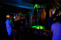 People dance on a makeshift stripper pole at Casey's Bar in downtown Whitefish, Montana, USA.  The bar's owners put a piece of wood over a pool table and connect a pole to the ceiling on busy nights at the bar.