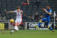 Callum Brittain of MK Dons clears the ball under pressure from Andy Barcham of AFC Wimbledon during the Sky Bet League 1 match between MK Dons and AFC Wimbledon at stadium:mk, Milton Keynes, England on 13 January 2018. Photo by David Horn.