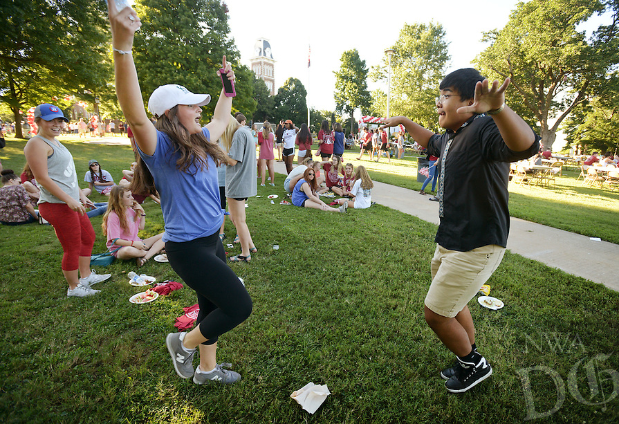 NWA Democrat-Gazette/BEN GOFF @NWABENGOFF<br /> Katie Hilburn, a freshman student from Carrollton, Texas, and Eizhar Anware, a freshman from China, dance on Sunday Aug. 21, 2016 during the New Student Welcome and Burger Bash event on Old Main Lawn on the University of Arkansas campus in Fayetteville.