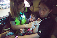 HONG KONG.<br /> SCHOOL BUS FEATURE:<br /> A young girl is treated by a medic in the back of Chen's car after being effected by tear gas during protests in the Mong Kok area of Hong Kong.<br /> 'School Buses', are the collective name to a group of volunteers, including Chen, who offer free transport for people who need help getting away from the protests safely.