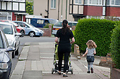 A woman with a pushchair and a child walks in a street in Burnt Oak, London.