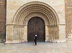 Woman standing by arched doorway of the cathedral church building in city of Valencia, Spain