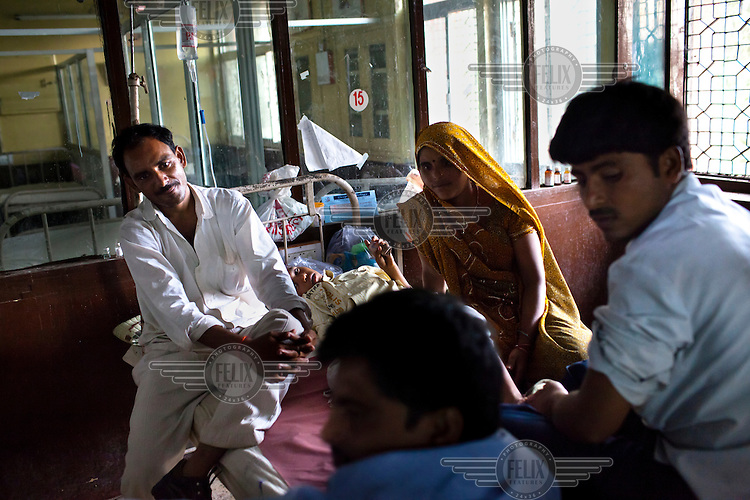 A family sit on the bed of a sick child in the pediatric ward at Maharani Laxmibai Medical College in Jhansi.