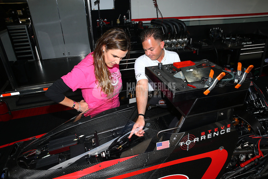 Apr 24, 2015; Baytown, TX, USA; NHRA top fuel driver Steve Torrence (right) explains the cockpit of his dragster with Taya Kyle , wife of US Navy sniper Chris Kyle in the pits during qualifying for the Spring Nationals at Royal Purple Raceway. Torrence announced a partnership with the Chris Kyle Frog Foundation. Mandatory Credit: Mark J. Rebilas-