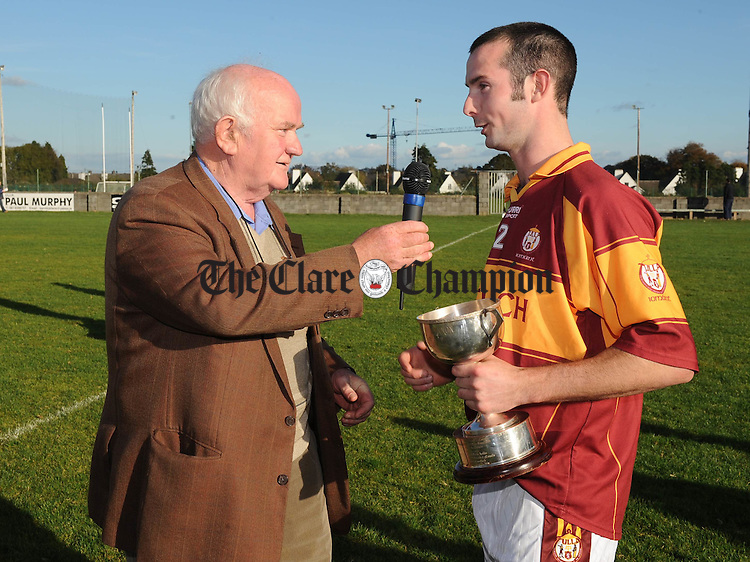 Tulla captain Eugene Cooney accepting the cup from Tom Burke, Clare GAA Irish Officer, after the Senior B final at Clarecastle. Photograph by John Kelly.
