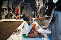 Shawna Williams, a senior art major from Hattiesburg, works on a mural on the back wall of the Dawg House stage in MSU's Colvard Student Union. The mural, which features Mississippi music with an emphasis on Black Prairie blues, is part of a larger remodeling of the Dawg House. The revamped space, which is currently used for a wide variety of events and as a lounge space, will be unveiled this fall. <br />