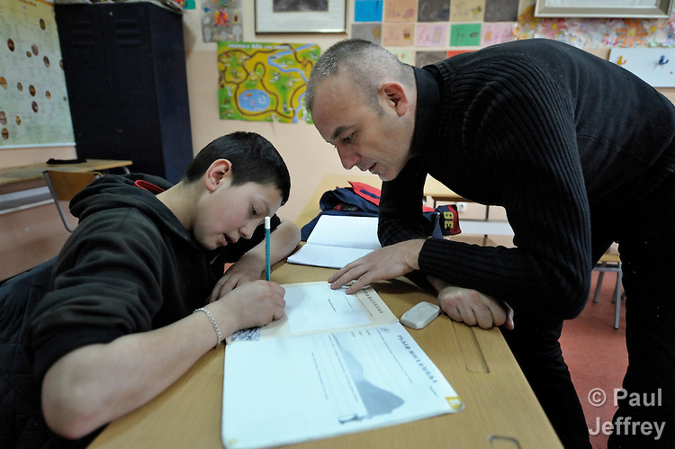 A teacher helps a boy during a class in the Branko Pesic School, an educational center for Roma children and families in Belgrade, Serbia, which is supported by Church World Service. Many of the students' families came to Belgrade as refugees from Kosovo. Many of them lack legal status in Serbia, and thus have difficulty obtaining formal employment and accessing government services.