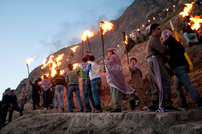 AKRE, IRAQ:  Kurdish men parade up Kele Mountain with torches...Newroz, celebrated across the world on the vernal equinox, is the official beginning of the Kurdish calendar and the first day of spring.  Kurds celebrate Newroz on March 20th and 21st by lighting fires and performing traditional dances...Photo by Kamaran Najm/ Metrography