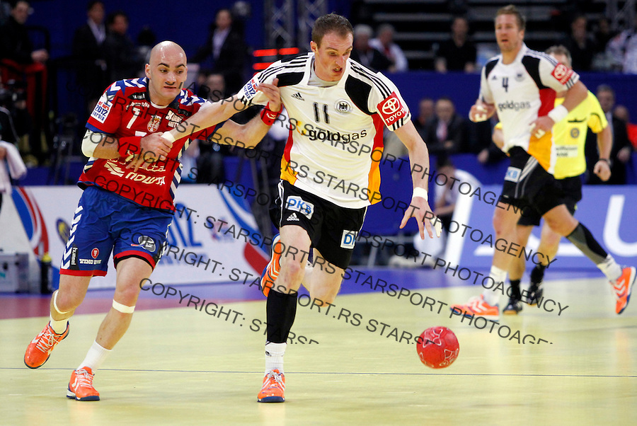 Holger Glandorf of Germany (R) is fouled by Ivan Nikcevic of Serbia during main round, group 1 men`s EHF EURO 2012 championship handball game between Serbia and Germany in Belgrade, Serbia, Saturday, January 21, 2011.  (photo: Pedja Milosavljevic / thepedja@gmail.com / +381641260959)