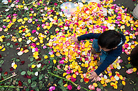 A child plays with colorful rose petals in the flower market of Bogota, Colombia, 10 July 2010. Colombia is one of the world leaders in cut flower industry. The advantage of the moderate sunny climate, very cheap labor force in combination with the absence of social laws and environmental regulations have created perfect conditions for the cut flower production. Flower growing is very fragile and necessarily depends on irrigation and chemical maintenance, provided by highly toxic pesticides. About 110.000 workers in Colombia, working mainly for living minimum wage, keep the floral industry going and saturate the market generated by consumerist culture the US, Canada and Europe.