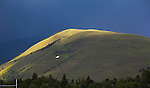 Sunlight shines on the top of Mount Jumbo on a dark cloudy day in Missoula, Montana