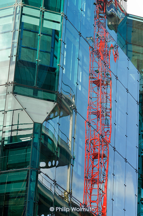A crane reflected in the glass cladding of a new office block in the City of London.