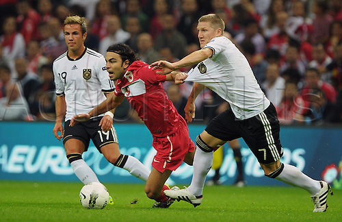 07.10.2011 Istanbul Turkey.  Germany's Mario Goetze (L) and Bastian Schweinsteiger (R) vie with Selcuk Inan (C) of Turkey during the EURO 2012 qualifying match between Turkey and Germany at the Turk Telekom Arena.