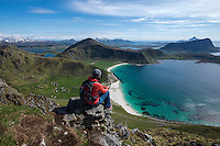 Female hiker on summit of Manen with Haukland beach in background, Vestvågøy, Lofoten Islands, Norway