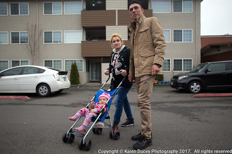 Shatha Sulaiman Kheder, (center), her husband Adil Kheder Nimr, (right) and their son Steven Adil Kheder, 10 months, outside their new apartment in Tukwila, Washington on January 30, 2017.  The family arrived in the United States on as refugees from Iraq on January 19, 2017, the day after Donald Trump was sworn in as the 45th president of the United States. They are concerned about thirteen of their family members still in Iraq. Trump signed an executive order last Friday restricting immigration from seven Muslim countries, suspending all refugee admission for 120 days, and bans all Syrian refugees indefinitely.  (Photo by Karen Ducey)