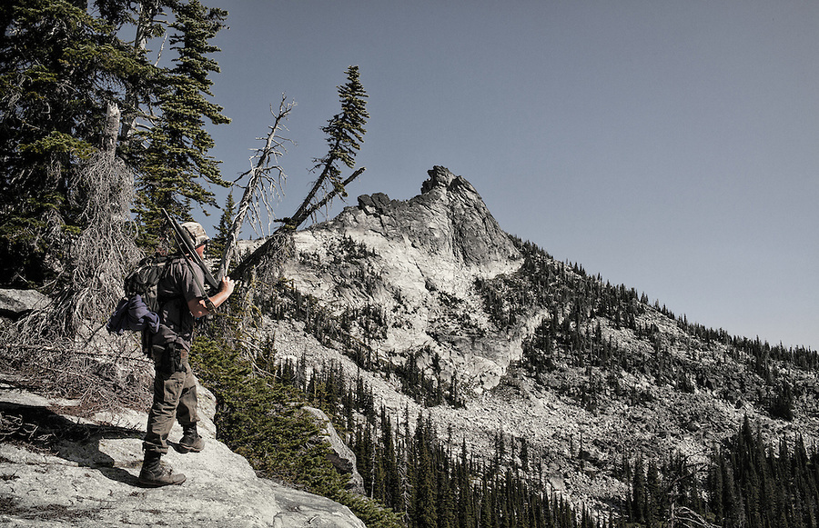 A man in his mid-30's looks over the edge of a cliff towards Harrison Peak in the Selkirks of Northern Idaho with a shotgun over his shoulder.