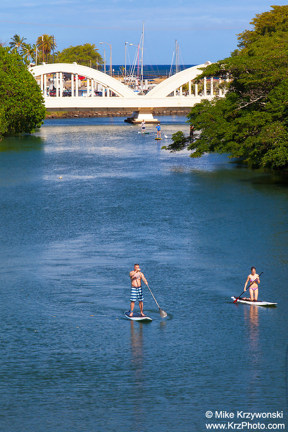 Man & woman stand-up Paddleboarding on Anahulu Stream in Haleiwa, North Shore, Oahu, Hawaii