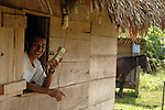 Man in his thatched hut with village's only phone in southern Belize.<br />