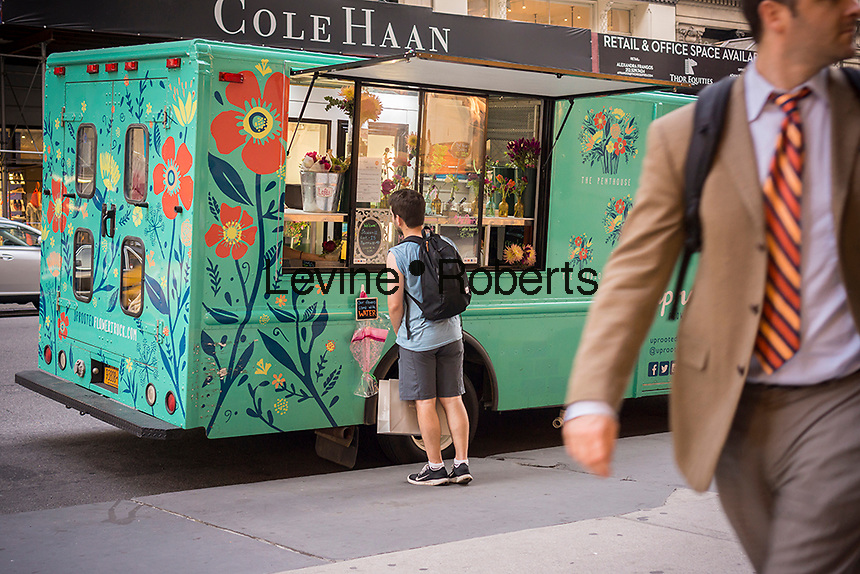 The Uprooted Flower Truck, a mobile florist, parks on Fifth Avenue in New York on Thursday, June 11, 2015. The truck parks in different locations and  sells hand-tied bouquets, different each day, in one of three sizes. The truck was financed with a Kickstarter campaign and is fully functional with a cooler, electrical system, hot water and of course, flowers.  (© Richard B. Levine)